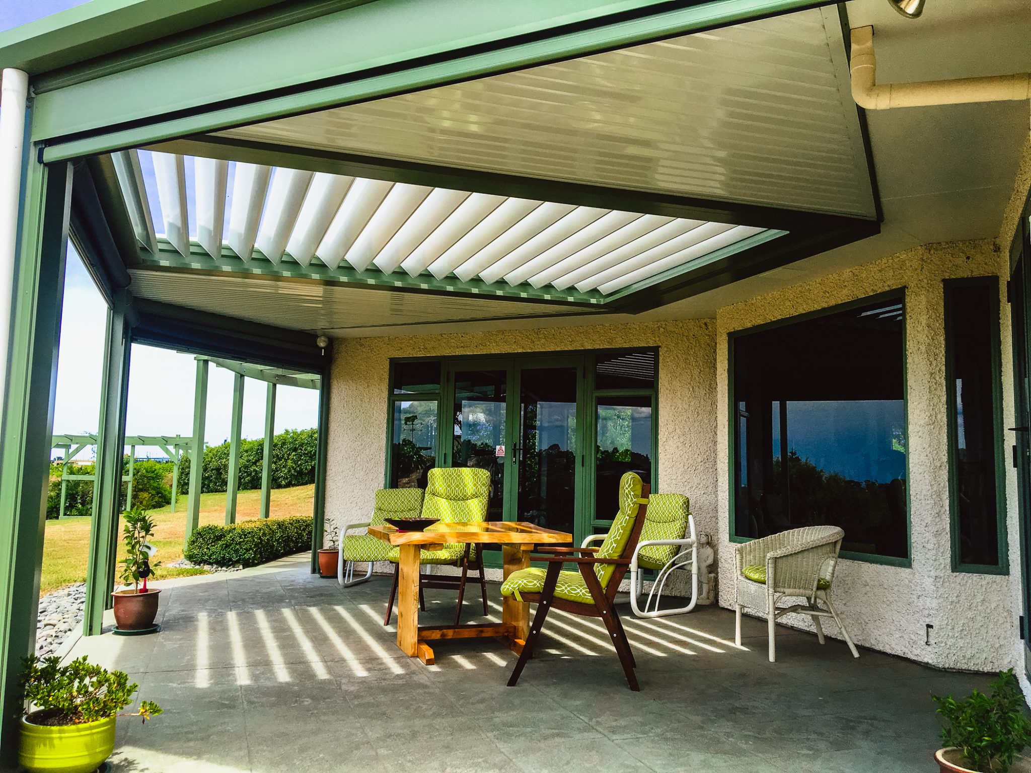 louvre roof surrounded by flat patio roof with louvre blades open and a dark green frame in hawkes bay, new zealand
