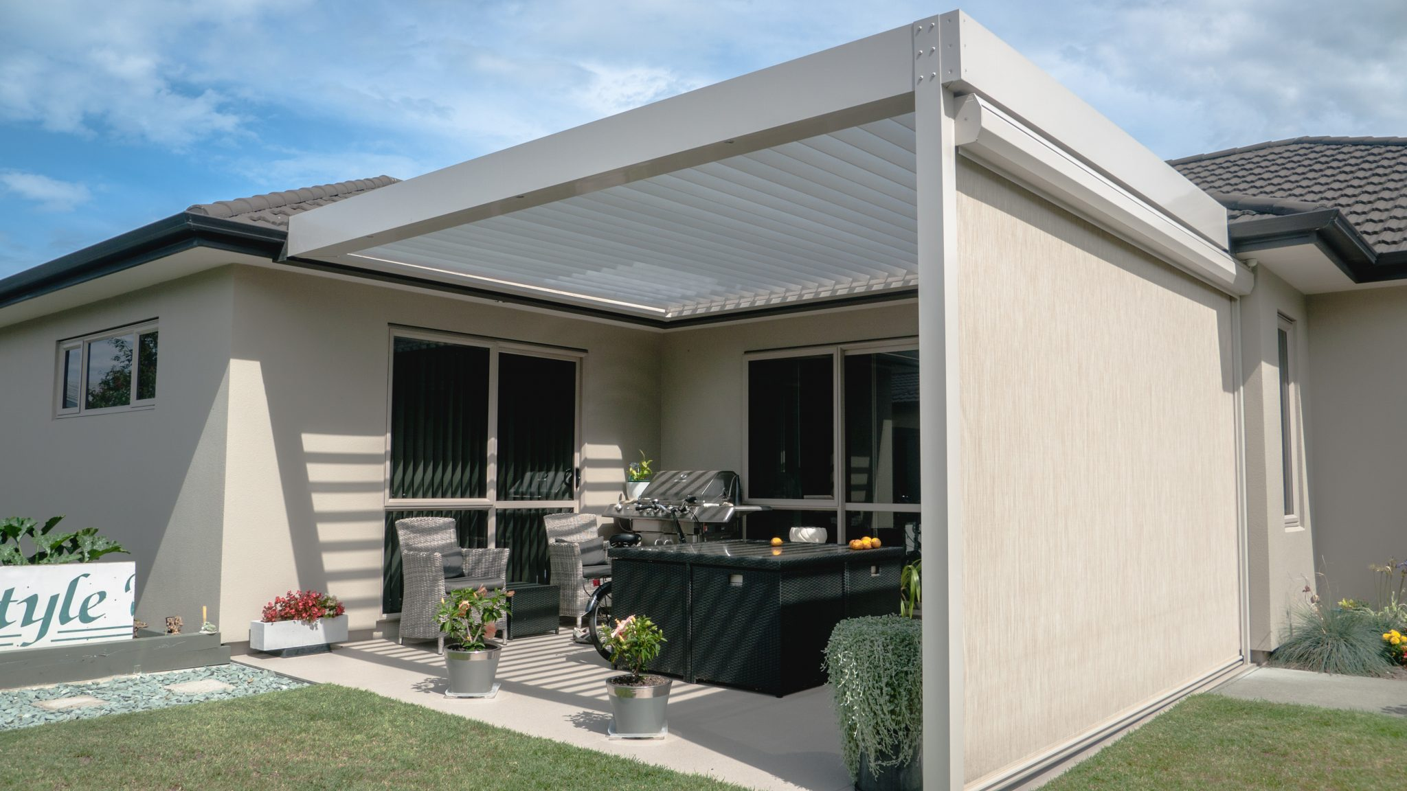 white louvre roof with open louvre blades, with white outdoor blind in parklands, napier