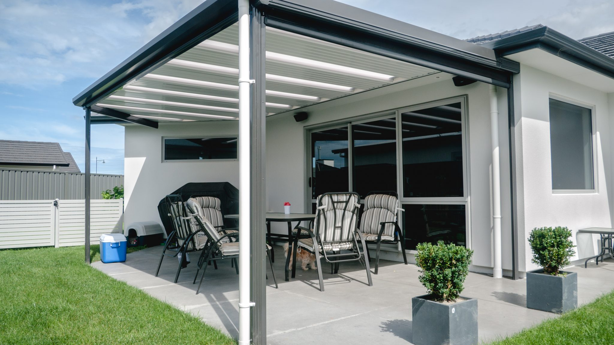 An outdoor dining area in parklands, napier sheltered by a beautiful pergola roof extension in white and grey colour scheme to match the houses existing colour scheme