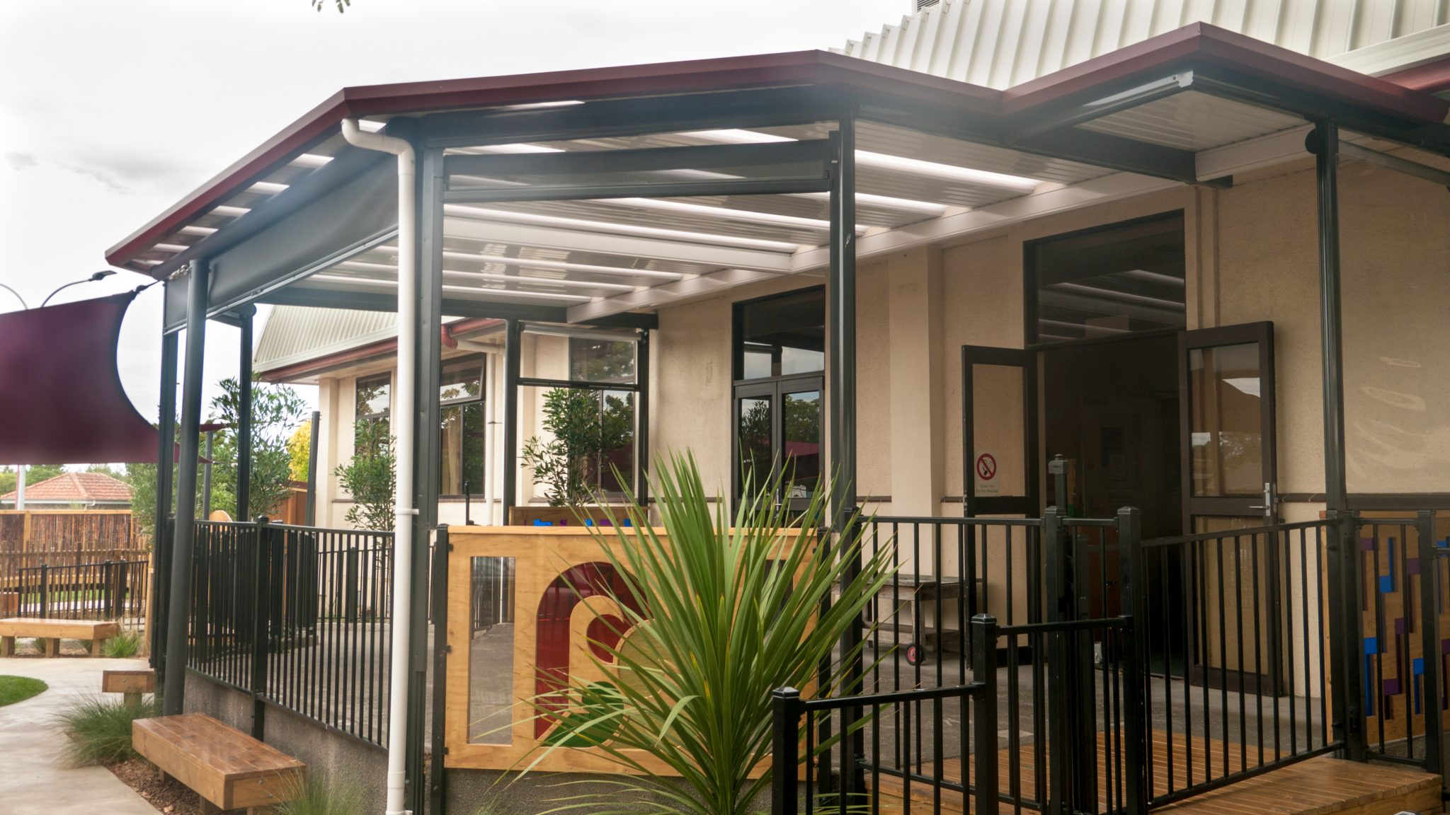 The outdoor area at the hawkes bay hospital featuring a big Stratco Flat Outback roof enclosed with Ziptrack outdoor blinds installed by Suncoast Patios Ltd