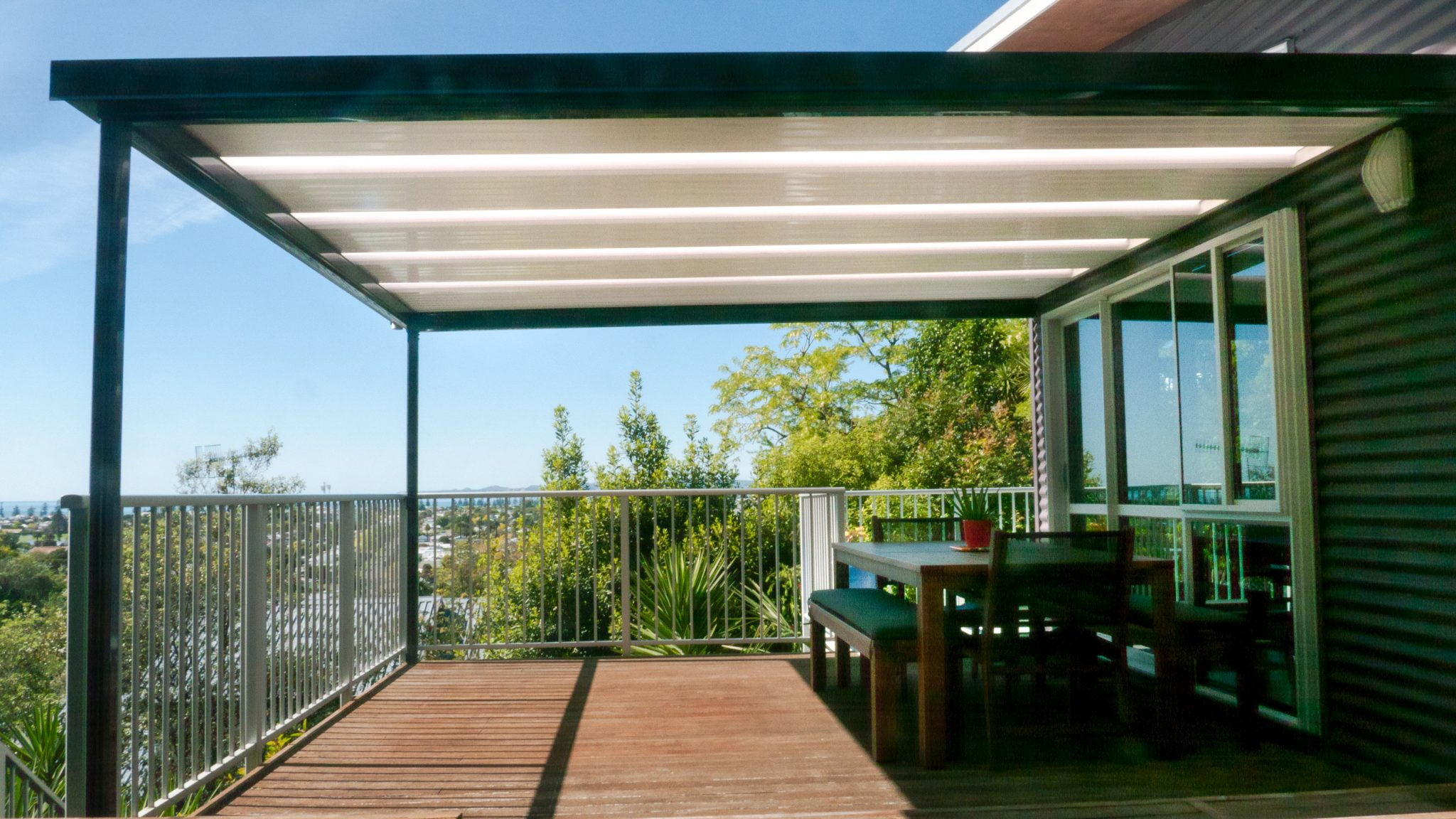 A Stratco Outback Flat pergola roof installed by Suncoast Patios Ltd on a deck with a beautiful view over napier from hospital hill
