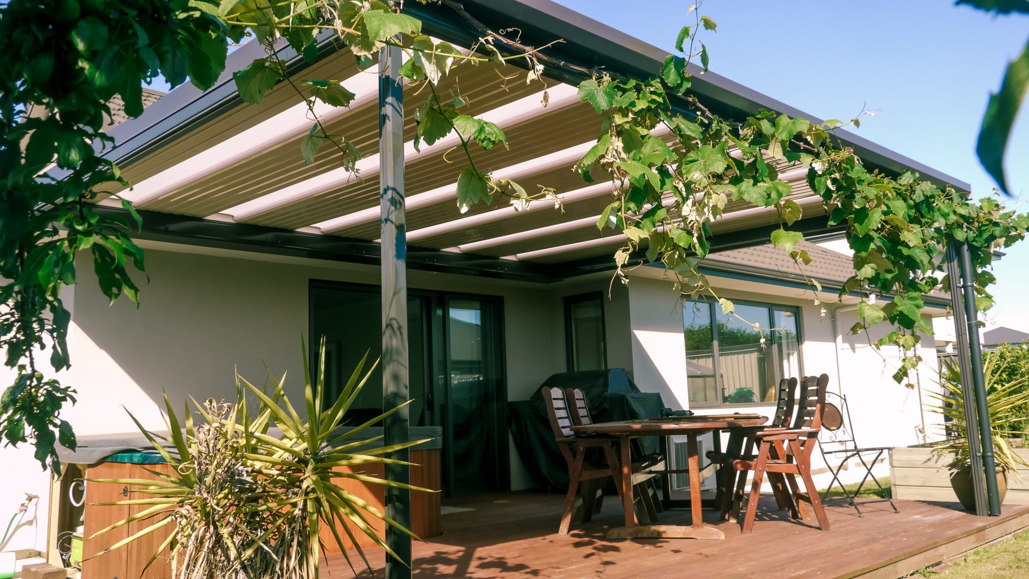 A cream coloured, flat pergola roof in hastings covering a deck with a spa pool, with vines growing around the outside of it